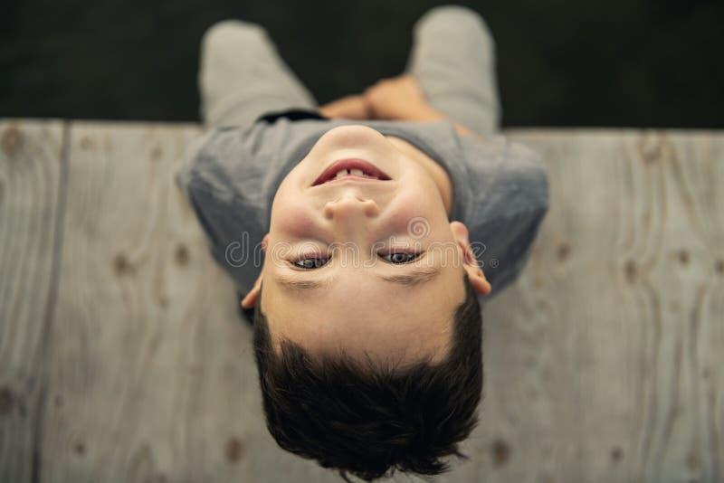Το μικρό παιδί κάθεται στην αποβάθρα zen όπως στοκ φωτογραφία