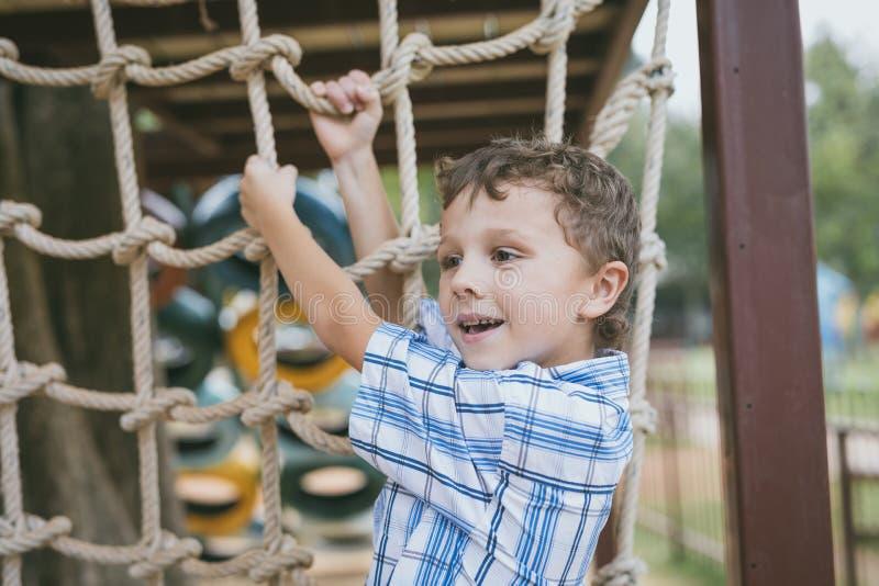 Το μικρό παιδί κάνει την αναρρίχηση στο πάρκο περιπέτειας στοκ φωτογραφία
