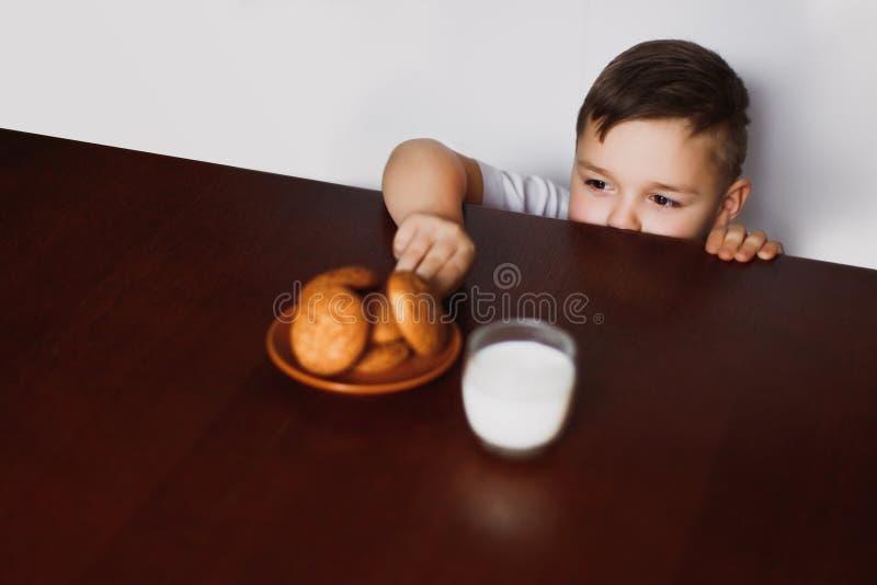 Το μικρό παιδί κλέβει τα μπισκότα στοκ φωτογραφία