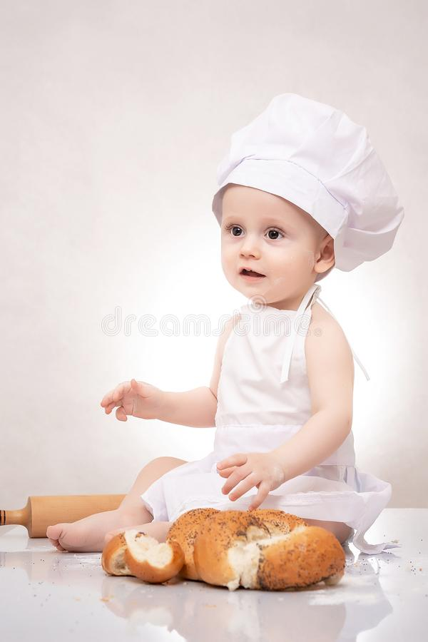 Το μικρό παιδί μαγειρεύει έναν croissant με το ψωμί να γελάσει ευτυχώς στοκ φωτογραφία με δικαίωμα ελεύθερης χρήσης