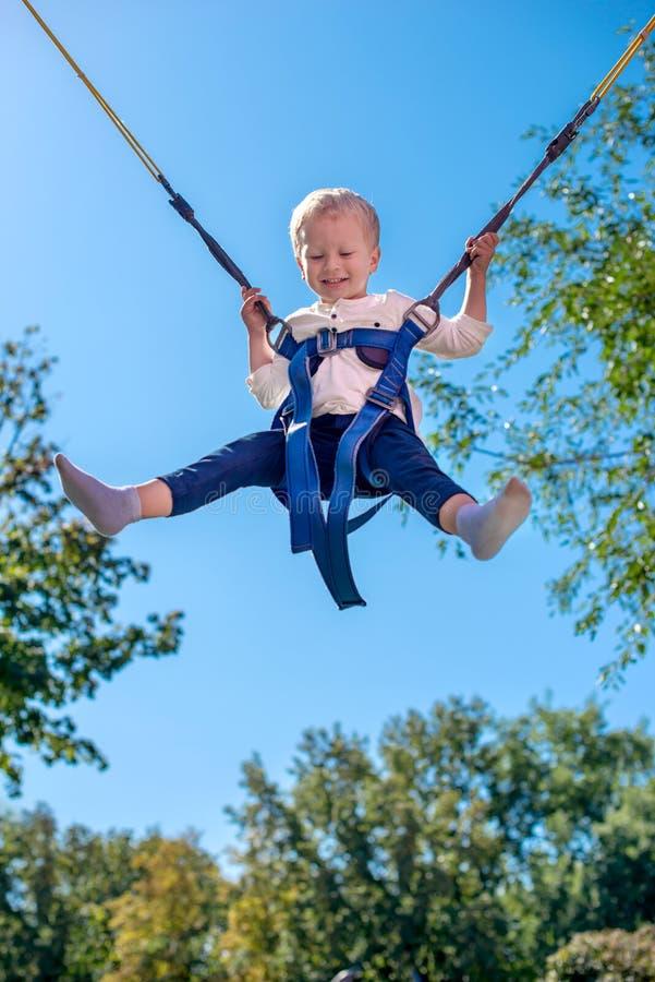 Το μικρό παιδί με τις ζώνες ασφαλείας σε μια έλξη στοκ εικόνες