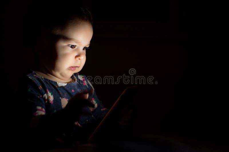 Το μικρό παιδί μωρών με το πρόσωπο άναψε από την τηλεφωνική οθόνη τη νύ στοκ εικόνες