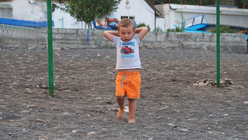 Το μικρό παιδί που περπατά στο αμμοχάλικο παραλιών Δραστηριότητα στη φύση κατά τη διάρκεια του υπολοίπου στην ακτή της θάλασσας στοκ εικόνα με δικαίωμα ελεύθερης χρήσης
