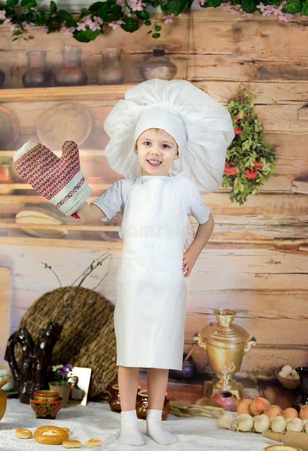 Το μικρό παιδί προετοιμάζει το κέικ και τις τηγανίτες Ντυμένη όπως τον αρχιμάγειρα μια ζύμη παιδιών προετοιμάζει τα τρόφιμα στοκ εικόνες με δικαίωμα ελεύθερης χρήσης