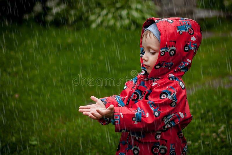 Το μικρό παιδί σε ένα αδιάβροχο σακάκι στα τρακτέρ πιάνει τη βροχή Παιδί που έχει τη διασκέδαση υπαίθρια στο θερινό ντους στοκ φωτογραφίες με δικαίωμα ελεύθερης χρήσης