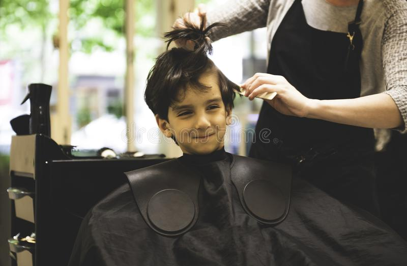 Το μικρό παιδί στην τρίχα καταστημάτων κουρέων έκοψε τον επαγγελματία στοκ φωτογραφία με δικαίωμα ελεύθερης χρήσης