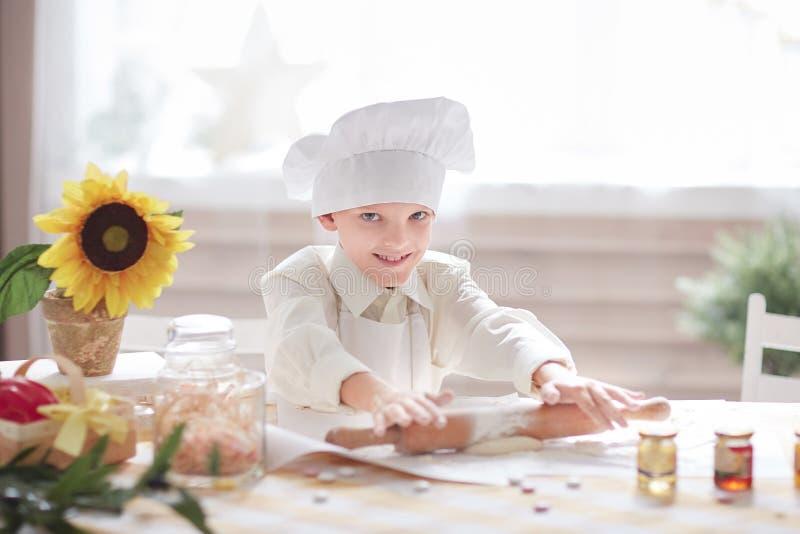 Το μικρό παιδί στο καπέλο ενός αρχιμάγειρα κυλά τη ζύμη στοκ εικόνα με δικαίωμα ελεύθερης χρήσης