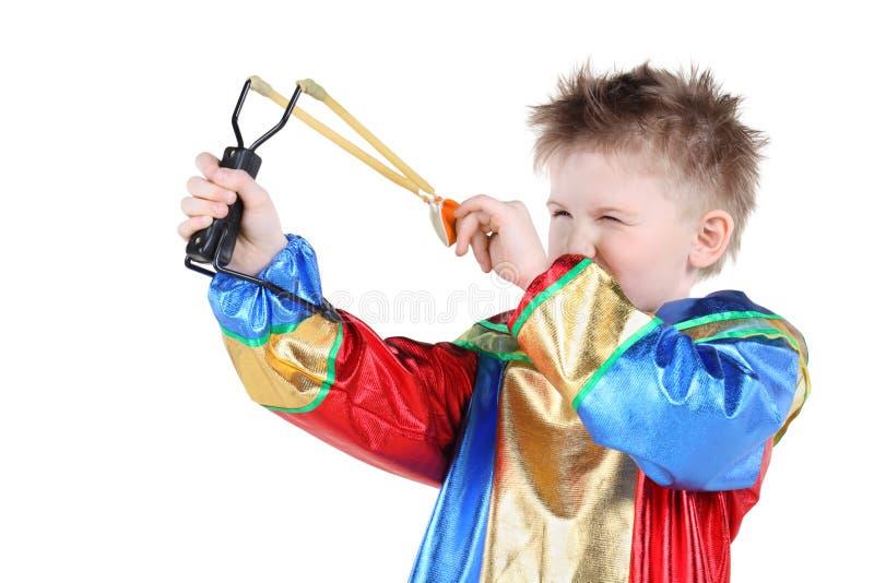 Το μικρό παιδί στο κοστούμι κλόουν κρατά slingshot και τους στόχους στοκ φωτογραφία