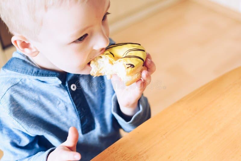 Το μικρό παιδί τρώει doughnut στοκ φωτογραφία