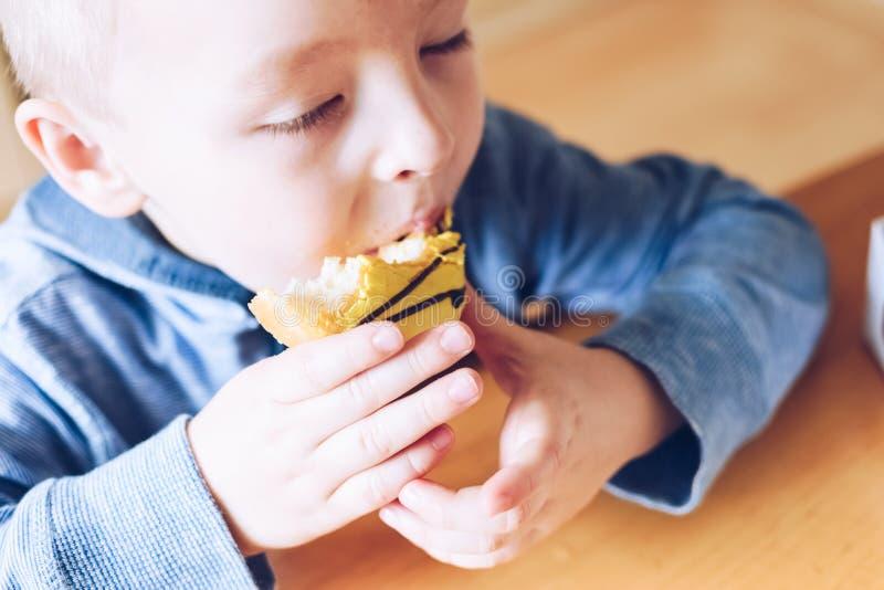 Το μικρό παιδί τρώει doughnut στοκ φωτογραφίες με δικαίωμα ελεύθερης χρήσης