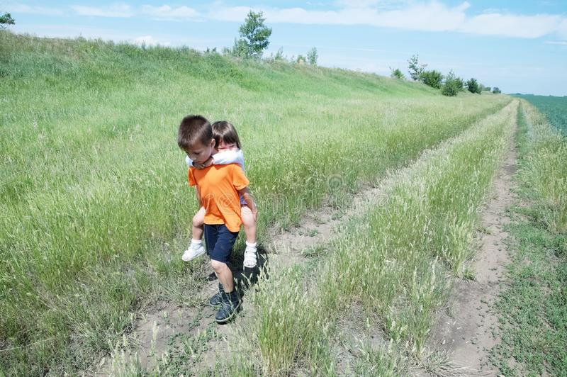 Το μικρό παιδί φέρνει λίγη αδελφή πίσω στο δρόμο στον τομέα στοκ εικόνες