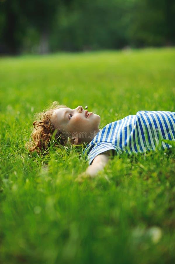 Το μικρό παιδί βρίσκεται σε έναν πράσινο χορτοτάπητα στο πάρκο στοκ εικόνες με δικαίωμα ελεύθερης χρήσης