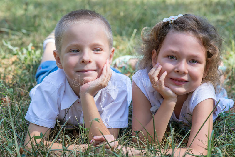 Το μικρό παιδί και το κορίτσι βρίσκονται μαζί σε μια χλόη στοκ εικόνες με δικαίωμα ελεύθερης χρήσης