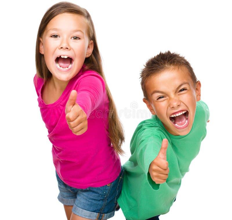 Το μικρό παιδί και το κορίτσι παρουσιάζουν ότι ο αντίχειρας υπογράφει επάνω στοκ εικόνες με δικαίωμα ελεύθερης χρήσης