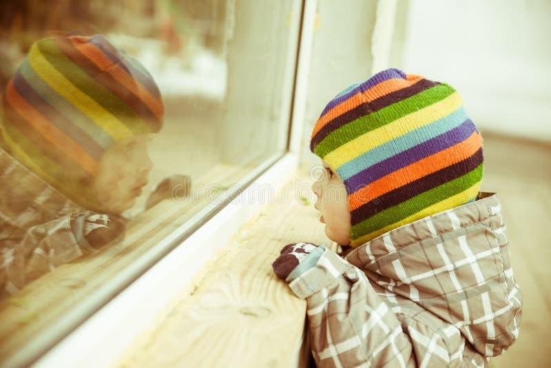 Το μικρό παιδί κοιτάζει στο παράθυρο στοκ φωτογραφίες με δικαίωμα ελεύθερης χρήσης
