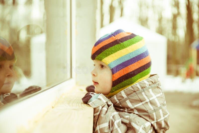 Το μικρό παιδί κοιτάζει στο παράθυρο στοκ φωτογραφία με δικαίωμα ελεύθερης χρήσης