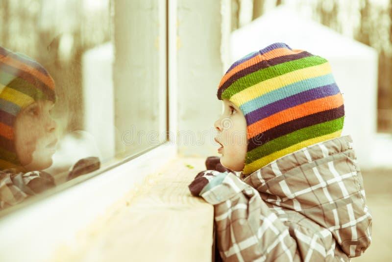 Το μικρό παιδί κοιτάζει στο παράθυρο στοκ φωτογραφίες