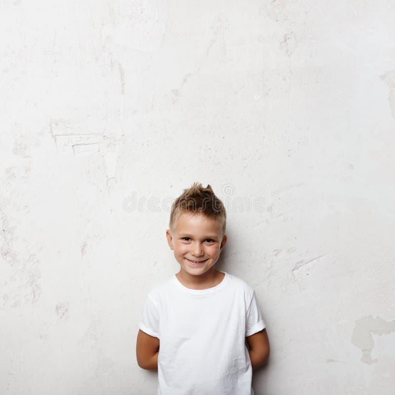 Το μικρό παιδί κρατά τα χέρια πίσω από πίσω και να χαμογελάσει επάνω στοκ φωτογραφίες