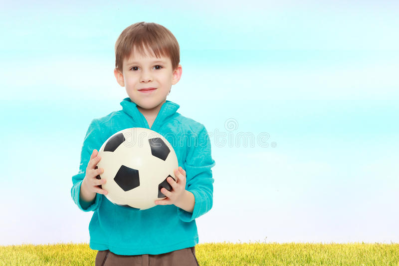 Το μικρό παιδί κρατά τη σφαίρα ποδοσφαίρου στοκ εικόνα