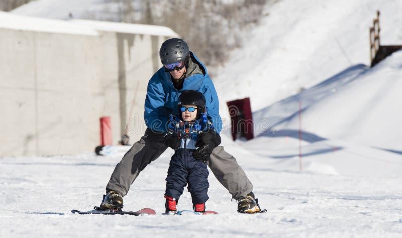 Το μικρό παιδί μαθαίνει να κάνει σκι με τον μπαμπά Ακίνδυνα ντυμένος στοκ εικόνα