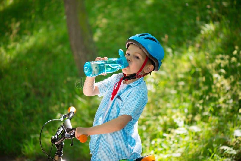 Το μικρό παιδί με το ποδήλατο πίνει το νερό στοκ φωτογραφία με δικαίωμα ελεύθερης χρήσης