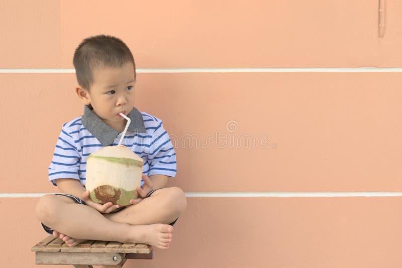 Το μικρό παιδί πίνει το νερό καρύδων στοκ εικόνες