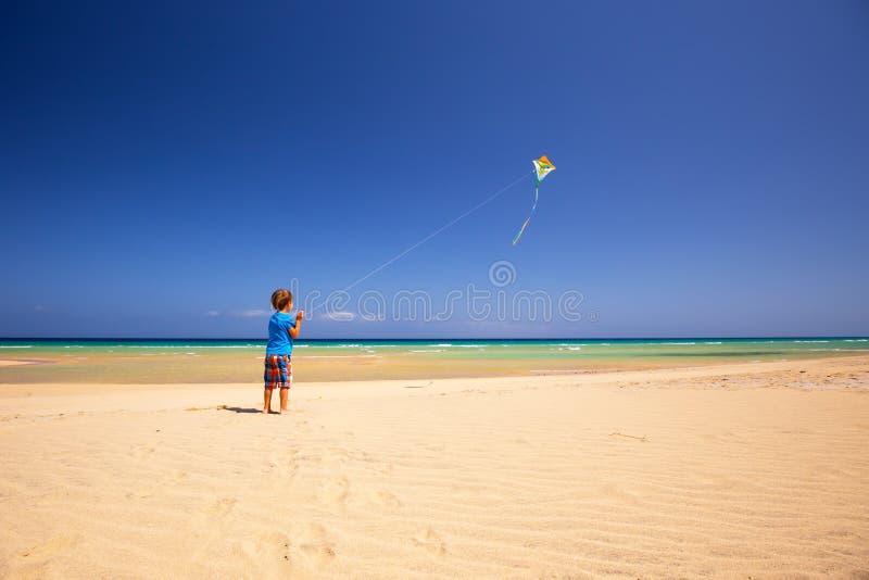 Το μικρό παιδί πετά έναν ικτίνο σε μια παραλία, Fuerteventura, Κανάρια νησιά, Ισπανία στοκ φωτογραφία