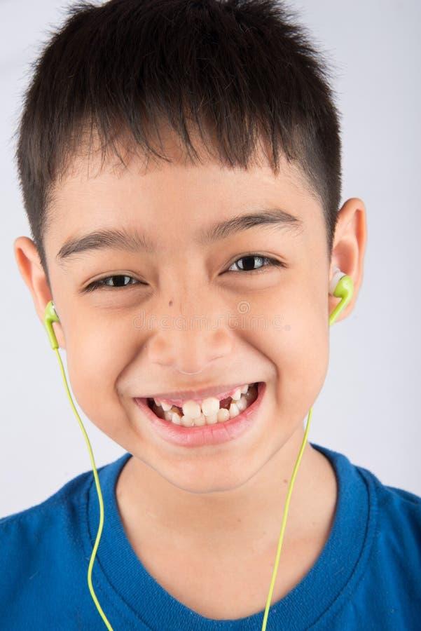 Το μικρό παιδί που χαμογελά χρησιμοποιώντας την κάσκα ακουστικών ακούει η μουσική στοκ φωτογραφία