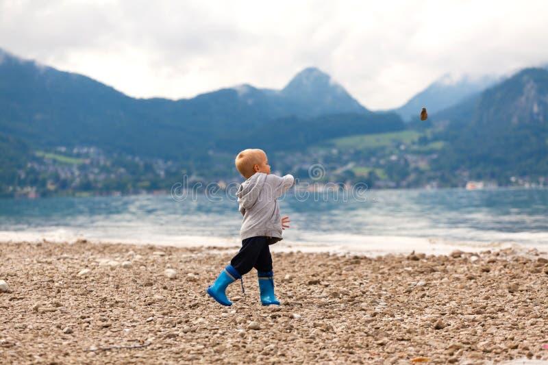 Το μικρό παιδί ρίχνει τις πέτρες στο νερό στοκ φωτογραφία με δικαίωμα ελεύθερης χρήσης