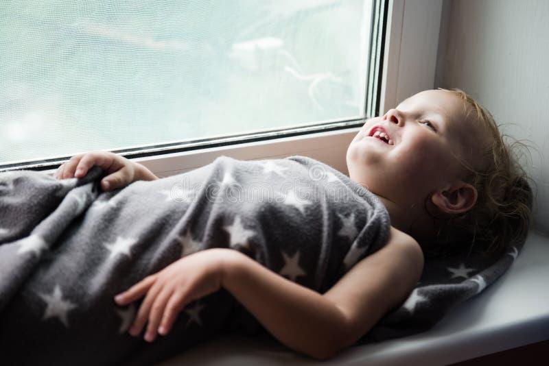 Το μικρό παιδί σε ένα windowsill στοκ εικόνες με δικαίωμα ελεύθερης χρήσης
