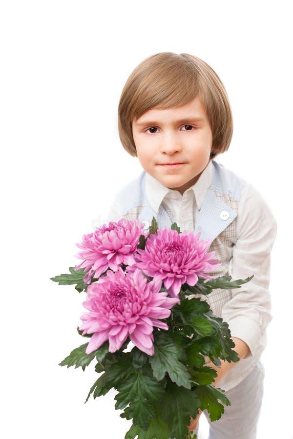 Το μικρό παιδί στέκεται με μια ανθοδέσμη ιώδες marguerite στοκ εικόνες