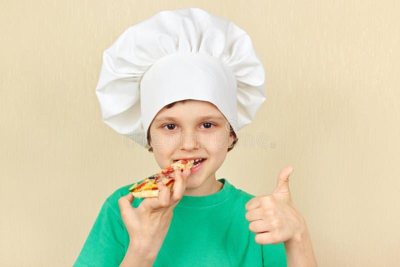 Το μικρό παιδί στο καπέλο αρχιμαγείρων δοκιμάζει τη μαγειρευμένη πίτσα στοκ φωτογραφίες