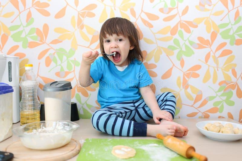 Το μικρό παιδί ψήνει στο σπίτι την κουζίνα στοκ φωτογραφίες