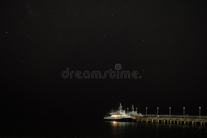 Το μικρό σκάφος αναψυχής έδεσε σε μια αποβάθρα κοντά στον έναστρο νυχτερινό ουρανό παραλιών πέρα από τη θάλασσα στοκ φωτογραφίες