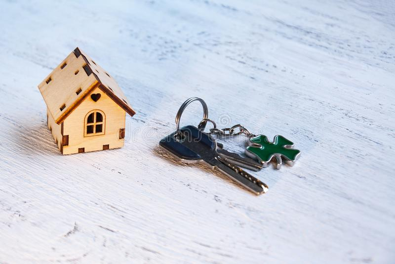 Το μικρό σπίτι δίπλα σε το είναι τα κλειδιά Σύμβολο της μίσθωσης ενός σπιτιού για το μίσθωμα, πώληση ενός σπιτιού, που αγοράζει έ στοκ φωτογραφία