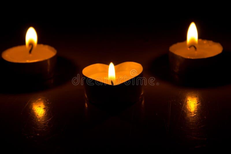 Το μικρό στρογγυλό κερί με την καρδιά-διαμορφωμένη ταμπλέτα ανάβει στο σκοτάδι στοκ φωτογραφίες