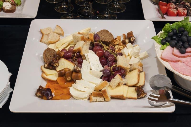 Το μικτό τυρί τεμαχίζει το άσπρο πιάτο στοκ φωτογραφία
