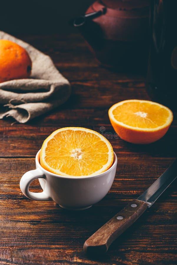 Το μισό από το πορτοκάλι σε ένα άσπρο φλυτζάνι στοκ εικόνες