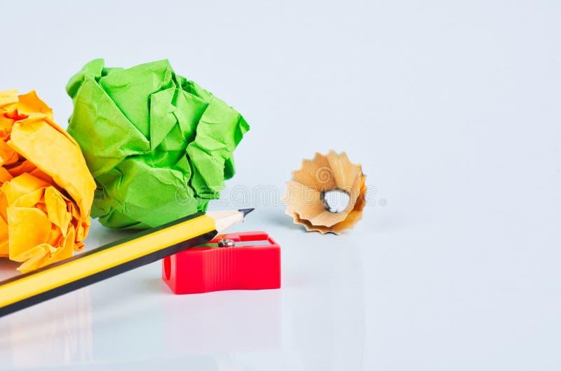 Το μολύβι με το ξέσματα, τσαλακώνει το έγγραφο και sharpener πέρα από το άσπρο υπόβαθρο στοκ φωτογραφία