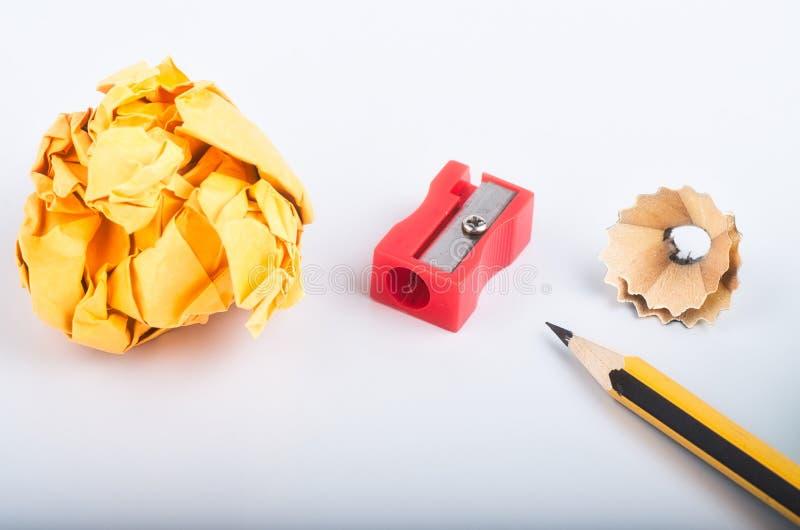 Το μολύβι με το ξέσματα, τσαλακώνει το έγγραφο και sharpener πέρα από το άσπρο υπόβαθρο στοκ εικόνες