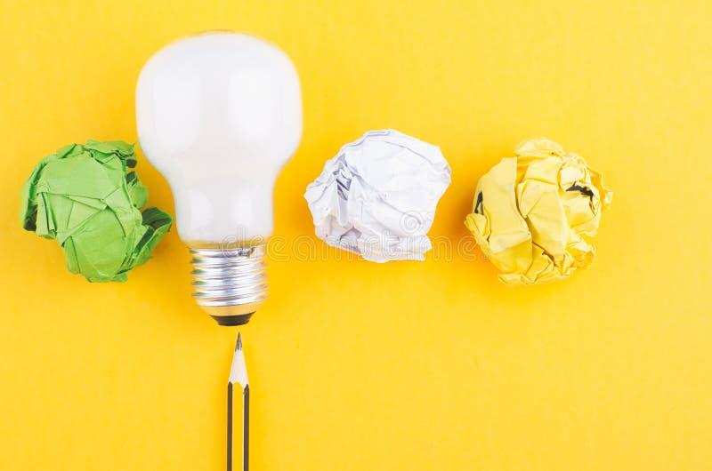 Το μολύβι, τσαλακώνει το έγγραφο και το βολβό πέρα από το κίτρινο υπόβαθρο στοκ εικόνα με δικαίωμα ελεύθερης χρήσης