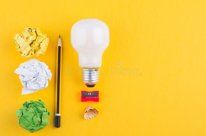 Το μολύβι, τσαλακώνει το έγγραφο και το βολβό πέρα από το κίτρινο υπόβαθρο στοκ φωτογραφία