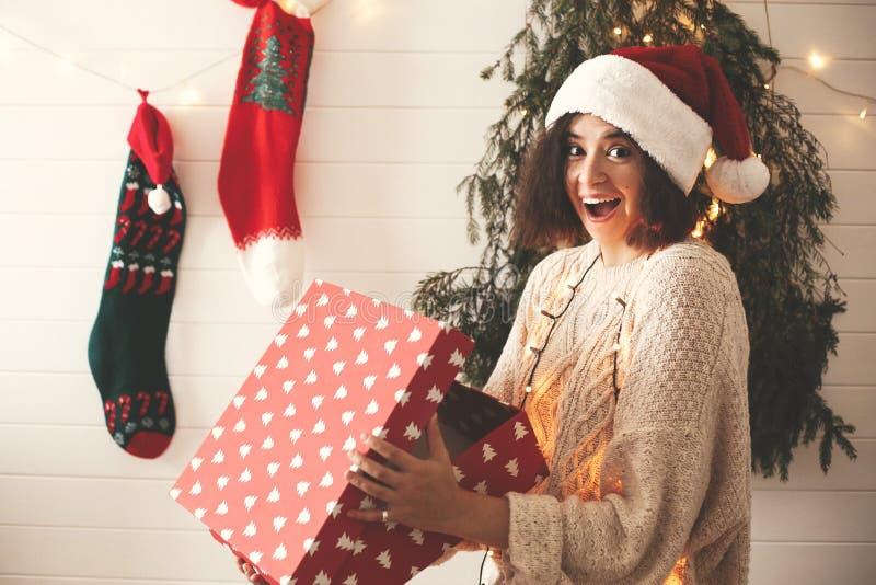 Το μοντέρνο έκπληκτο κορίτσι στο κιβώτιο δώρων ανοίγματος καπέλων santa στα Χριστούγεννα διακόσμησε το δωμάτιο Νέα γυναίκα στο εο στοκ εικόνες