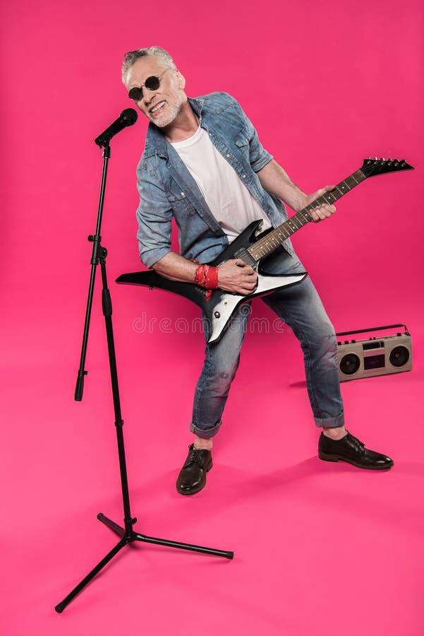 Το μοντέρνο ανώτερο άτομο στα γυαλιά ηλίου που παίζει το βράχο - και - κυλά τη μουσική με την ηλεκτρική κιθάρα στοκ εικόνες
