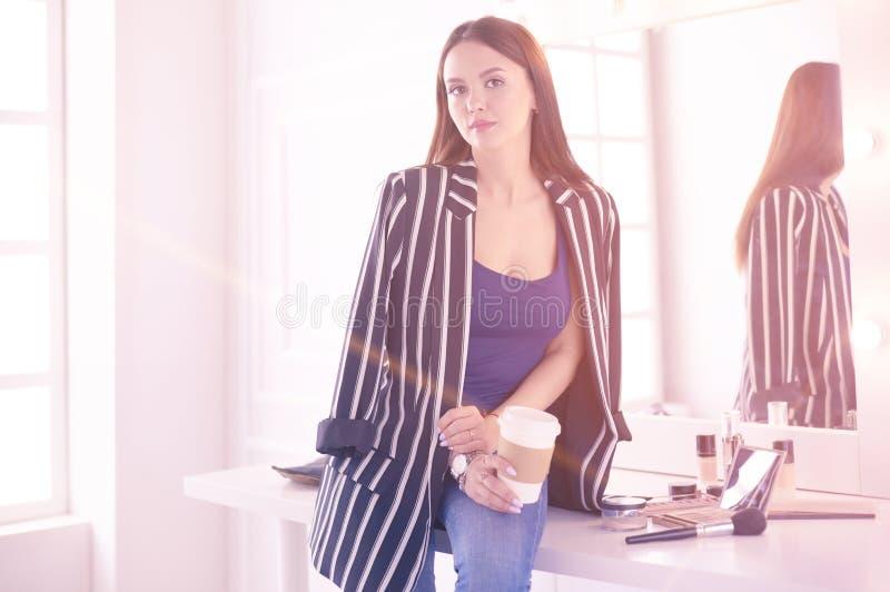 Το μοντέρνο θηλυκό αποτελεί το φλυτζάνι κατανάλωσης καλλιτεχνών του cappuccino και αναμονή τους επισκέπτες στο σύγχρονο εσωτερικό στοκ φωτογραφία με δικαίωμα ελεύθερης χρήσης
