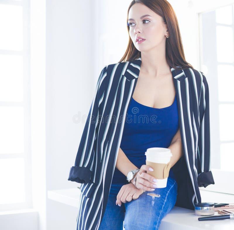 Το μοντέρνο θηλυκό αποτελεί το φλυτζάνι κατανάλωσης καλλιτεχνών του cappuccino και αναμονή τους επισκέπτες στο σύγχρονο εσωτερικό στοκ εικόνες