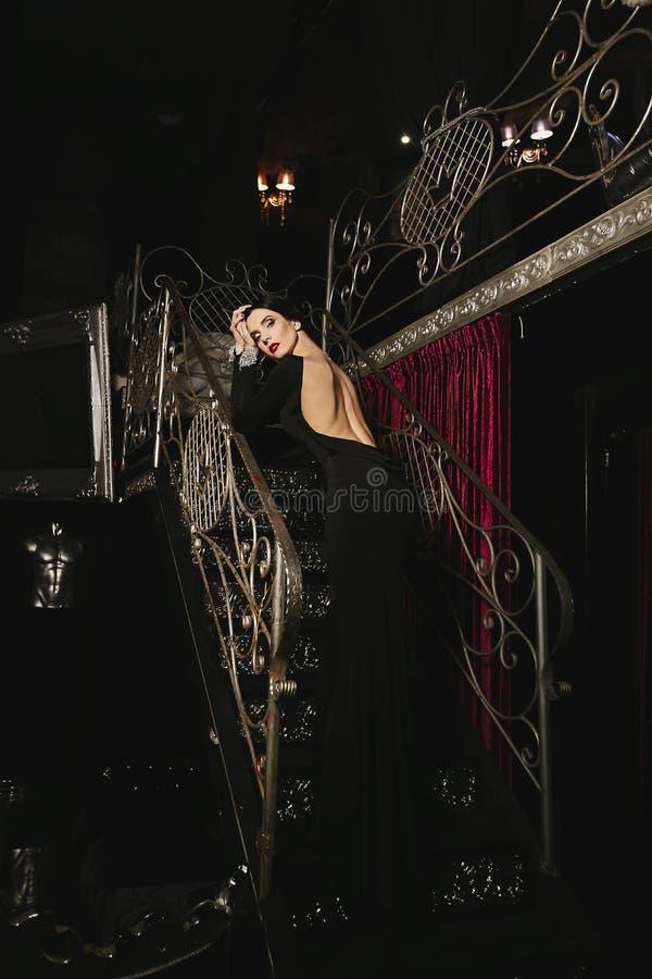 Το μοντέρνο και προκλητικό πρότυπο κορίτσι brunette με το τέλειο σώμα και τα κόκκινα χείλια το μαύρο βράδυ ντύνουν με τη nude πίσ στοκ εικόνα