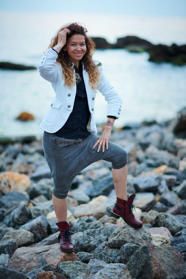 Το μοντέρνο κορίτσι έντυσε στο άσπρο σακάκι και το ευρύ παντελόνι που θέτουν κοντά στη θάλασσα το βράδυ στοκ εικόνα