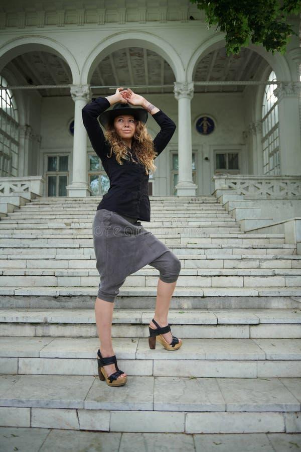 Το μοντέρνο κορίτσι έντυσε στο μαύρο πουκάμισο, το καπέλο και το ευρύ παντελόνι που θέτουν κοντά στον παλαιό Λευκό Οίκο στοκ φωτογραφίες