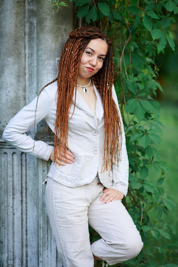 Το μοντέρνο κορίτσι Dreadlocks έντυσε στην άσπρη τοποθέτηση κοντά στις αναδρομικές στήλες στοκ φωτογραφία με δικαίωμα ελεύθερης χρήσης